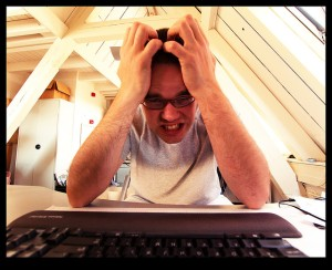 A frustrated man pulls his hair over a computer screen